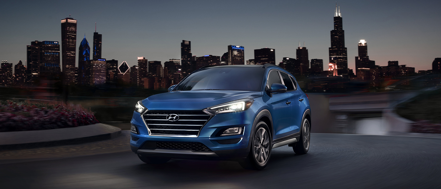 Blue 2019 Hyundai Tucson in front of a city skyline