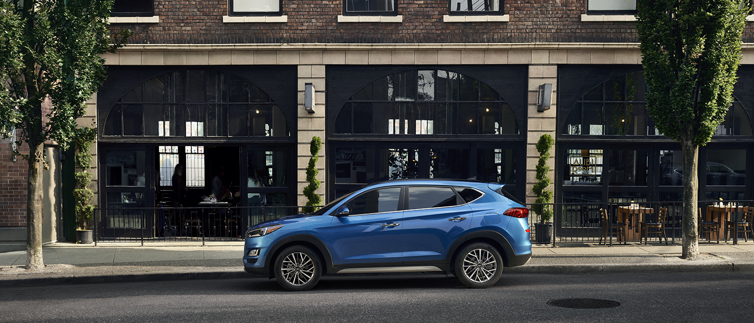 Profile view of a blue 2019 Hyundai Tucson parked in front of a building