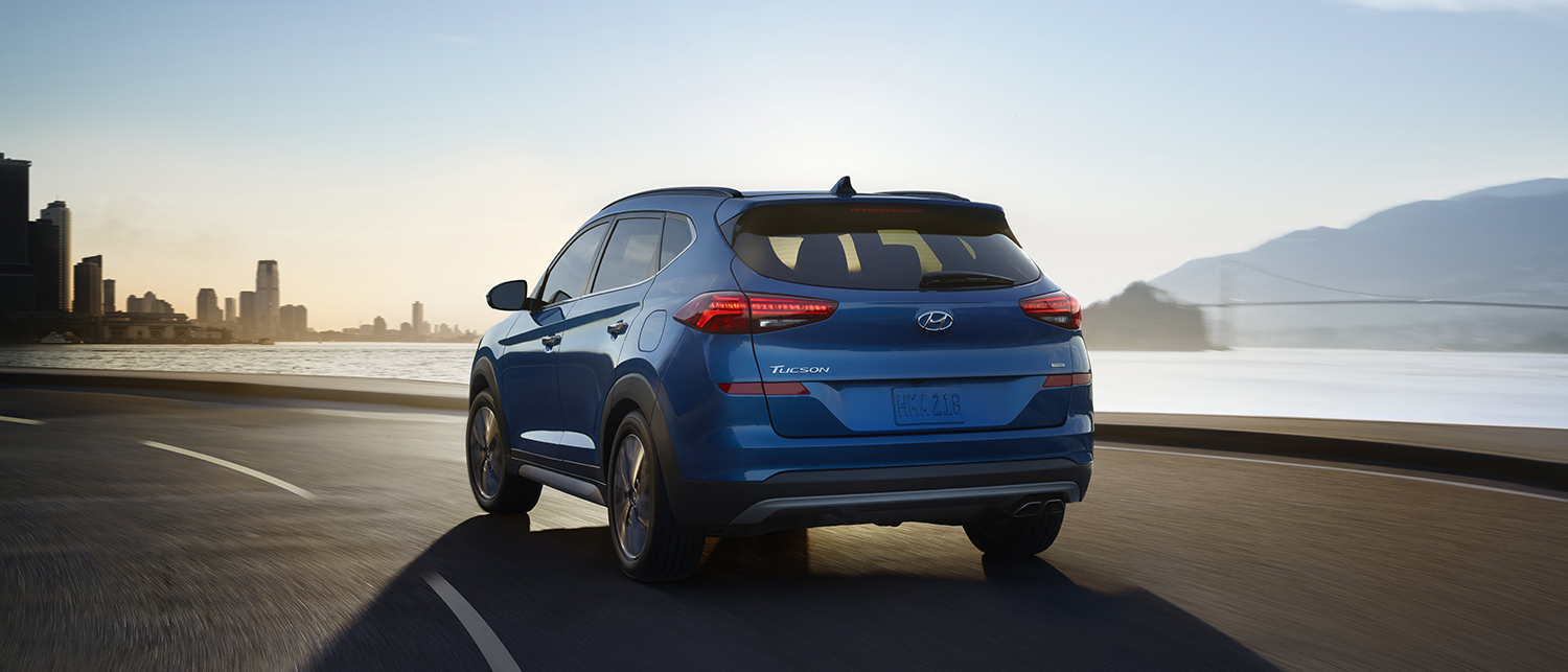 Blue Hyundai Tucson driving away on scenic road