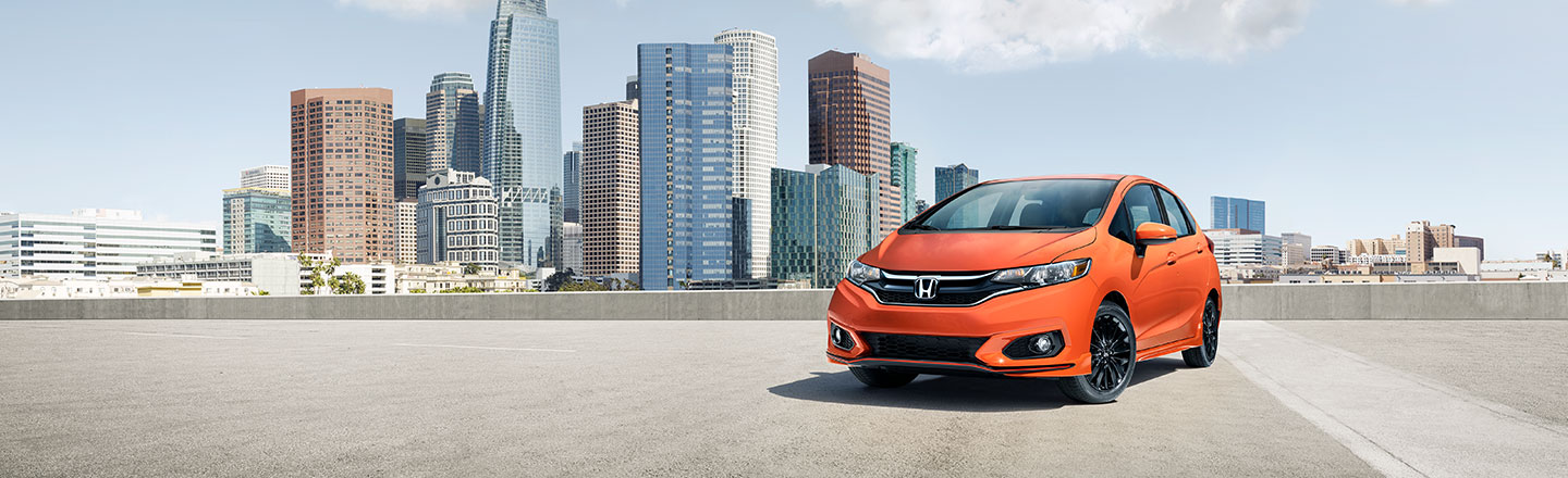 Honda Fit parked along garage rooftop with city skyline in background