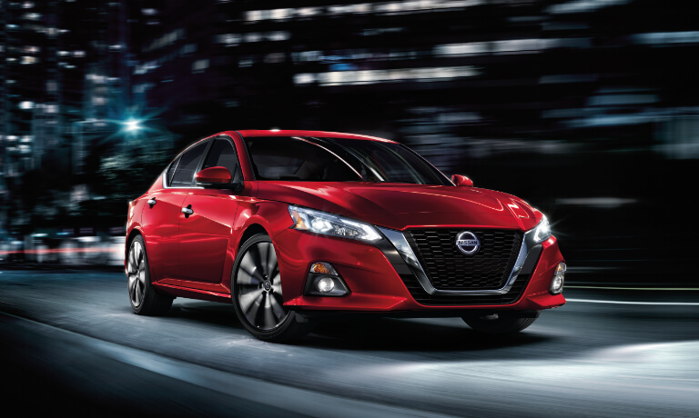 2019 Nissan Altima driving through city at night