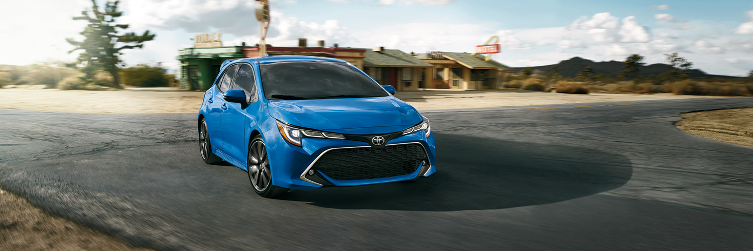 Blue 2019 corolla hatchback parked at a crossroads