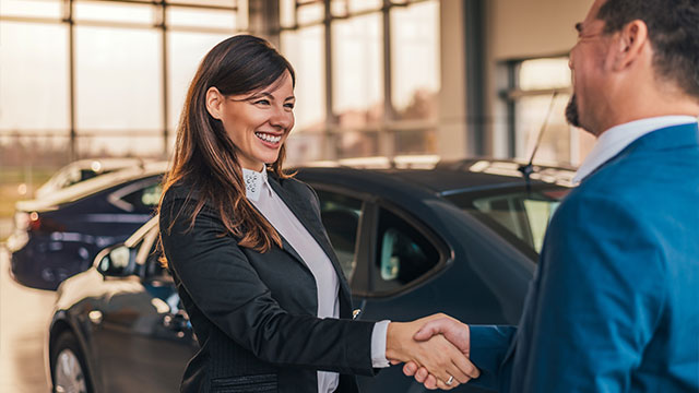 Smiling customer shaking hands with dealer in front of car