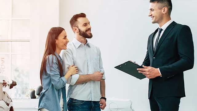 Young couple speakinbg to salesman