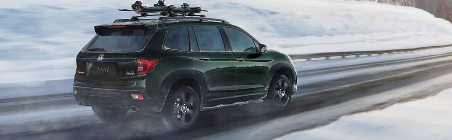 Green 2019 Honda Passport Driving in the snow
