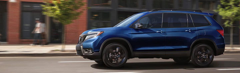 Blue Honda Passport Driving Down The Road