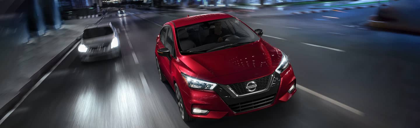 The 2020 Nissan Versa in red driving on the road