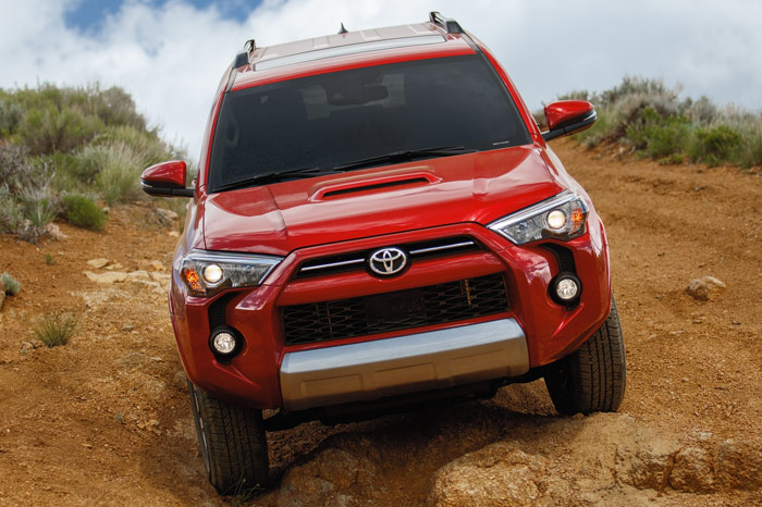 Front of Red Toyota 4Runner driving through rough terrain