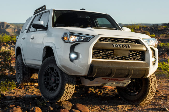 Front-Right of White Toyota 4Runner driving through rough terrain