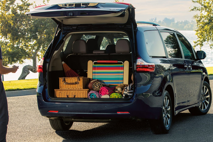 Open trunk full of luggage and picnic gear in the back of a blue Toyota Sienna