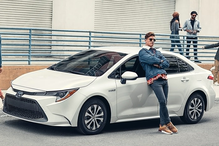 Man with sun-glasses leaning on white Toyota Corolla Hybrid