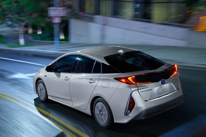 Back end of white Toyota Prius Prime driving through public roads
