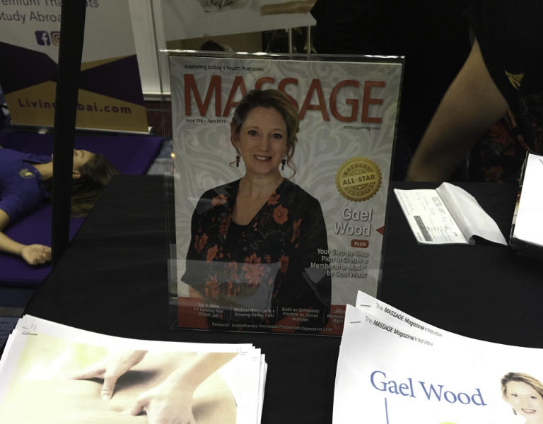 A display with a copy of Massage Magazine, Gael featured on the cover as their All-Star