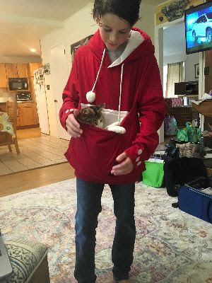 My son, in red hoodie, carrying cat