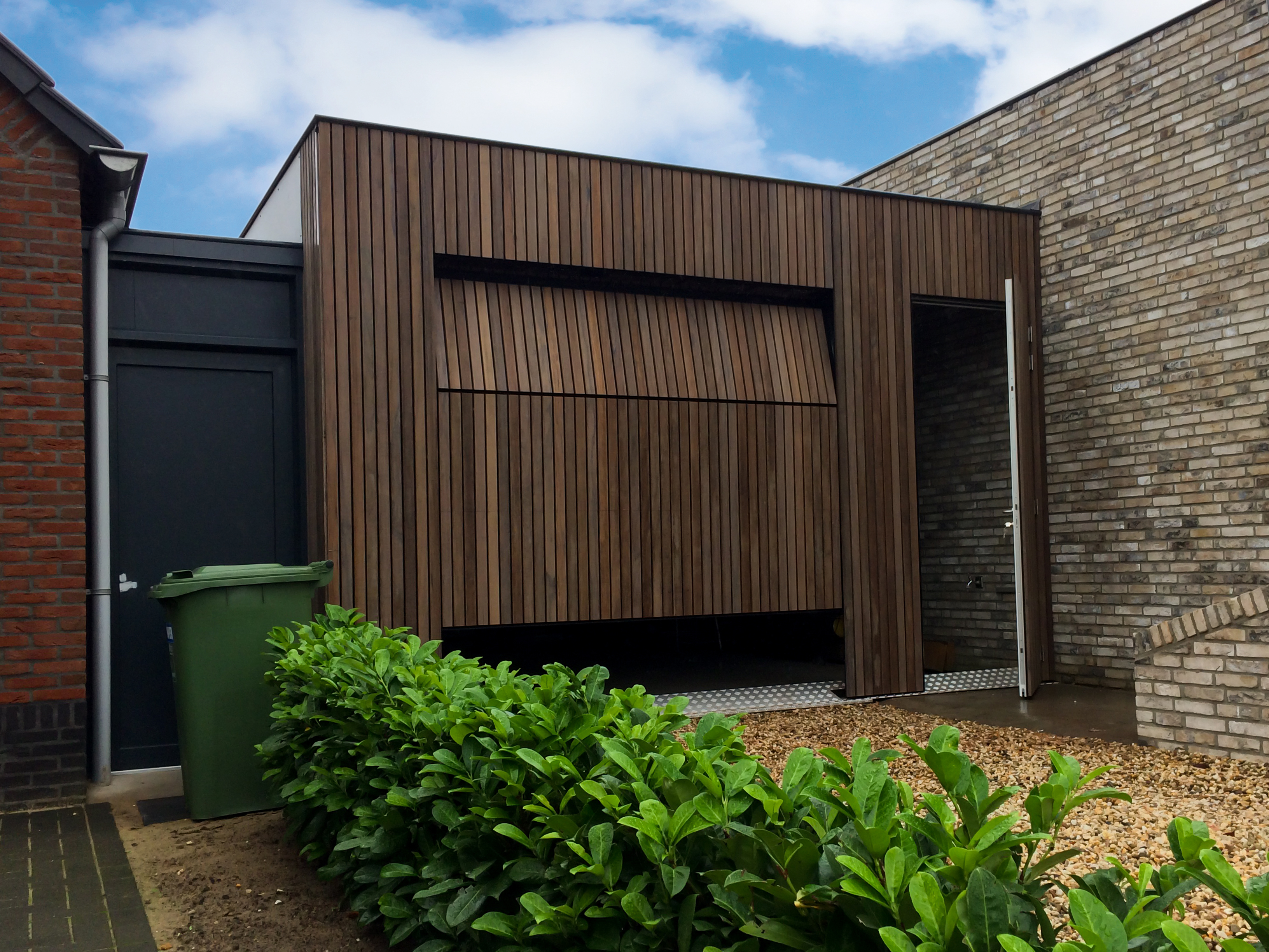 Verticale plato garagedeur gelijk in de gevel met loopdeur