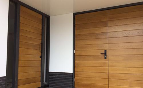 Houten voordeur en garagedeur in dezelfde stijl