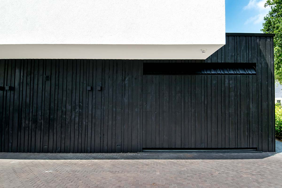 Zwarte-houten-garagedeur-verticaal-geprofileerd-in-drie-breedtes-gelijk-met-gevel-1