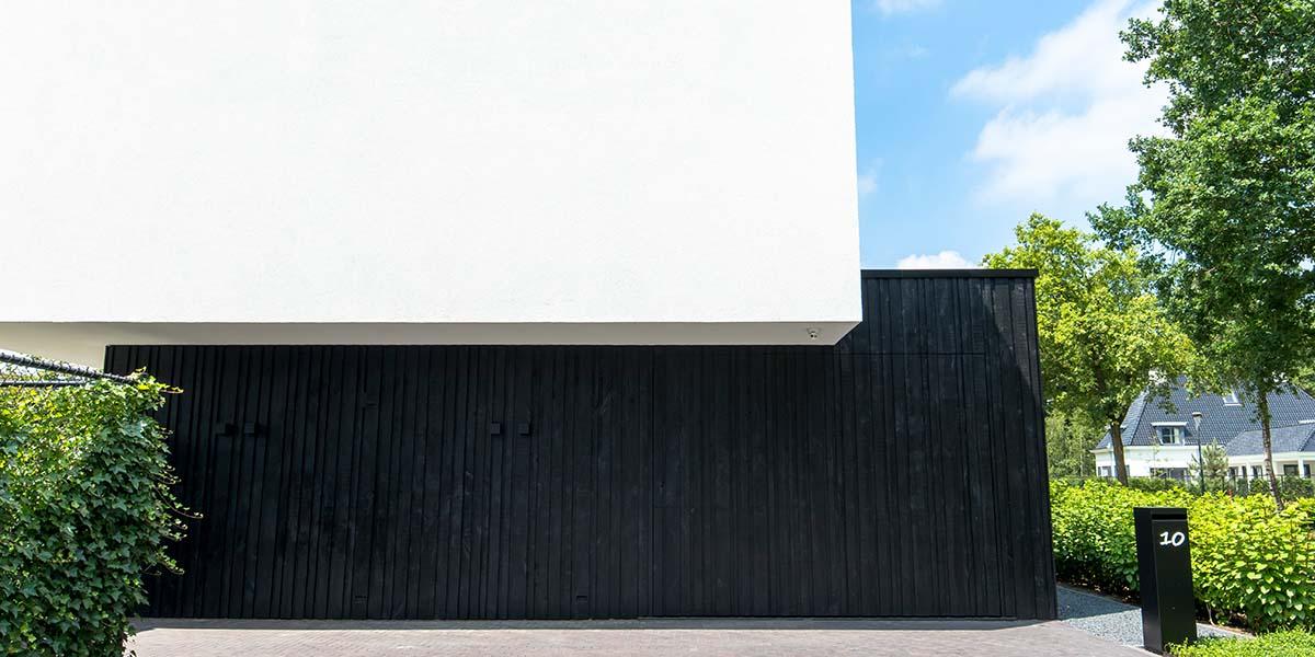 Zwarte-houten-garagedeur-verticaal-geprofileerd-in-drie-breedtes-gelijk-met-gevel-26