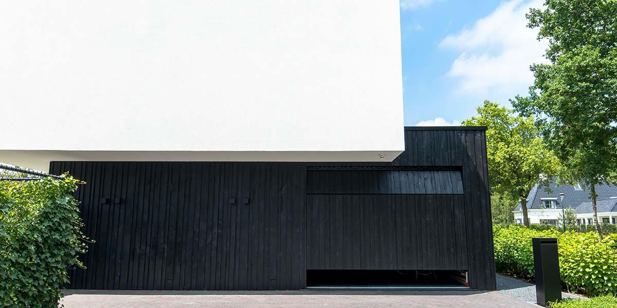 Zwarte-houten-garagedeur-verticaal-geprofileerd-in-drie-breedtes-gelijk-met-gevel-27