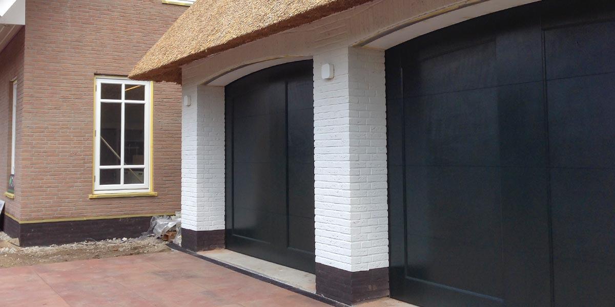 Twee-houten-garagedeuren-bij-rieten-kap-woning