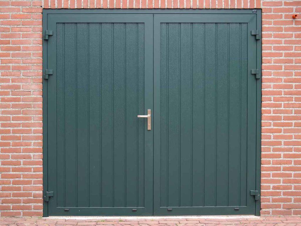 Donkergroene openslaande garagedeur voorzien van houtnerf verticaal