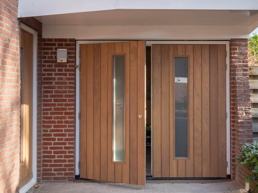 Houten openslaande garagedeur van Afrormosia hout. Voorzien van verticaal melkglas.