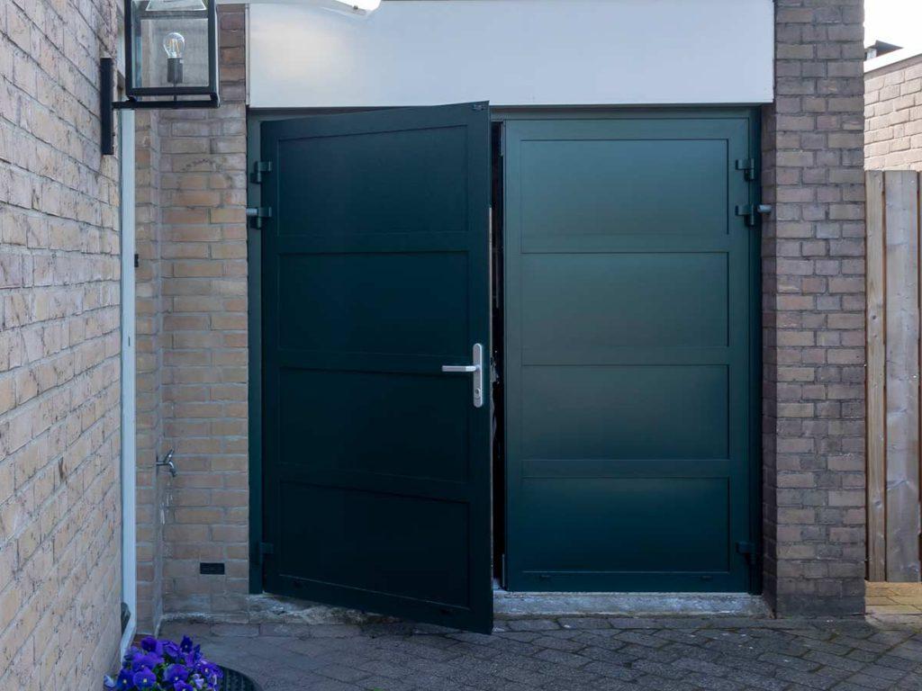 Groene geïsoleerde openslaande garagedeur