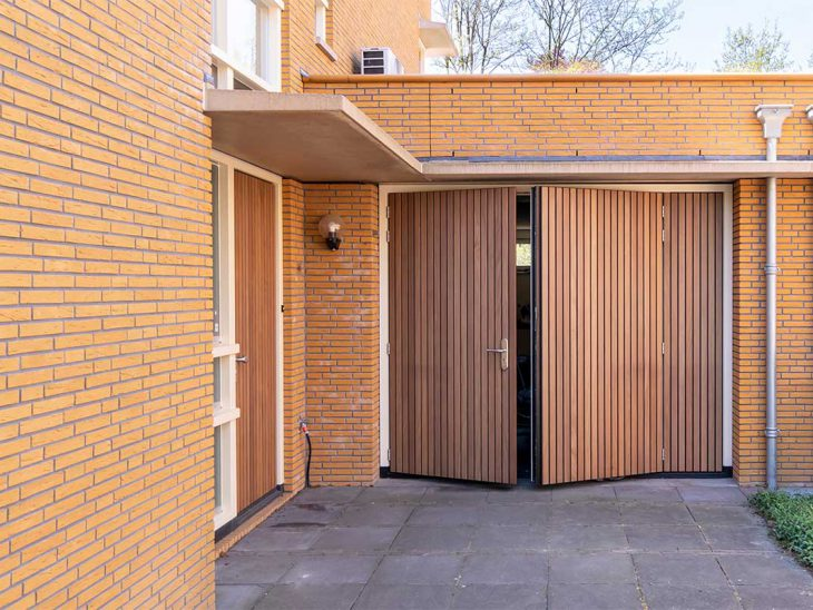 Verticale houten voordeur met houten openslaande garagedeur