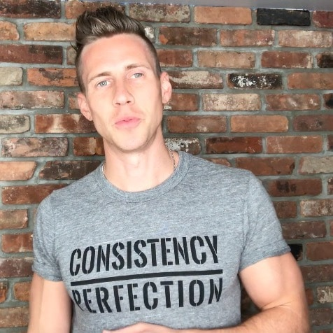 "Mike Vacanti wearing a grey shirt which reads, ""Consistency Over Perfection"""