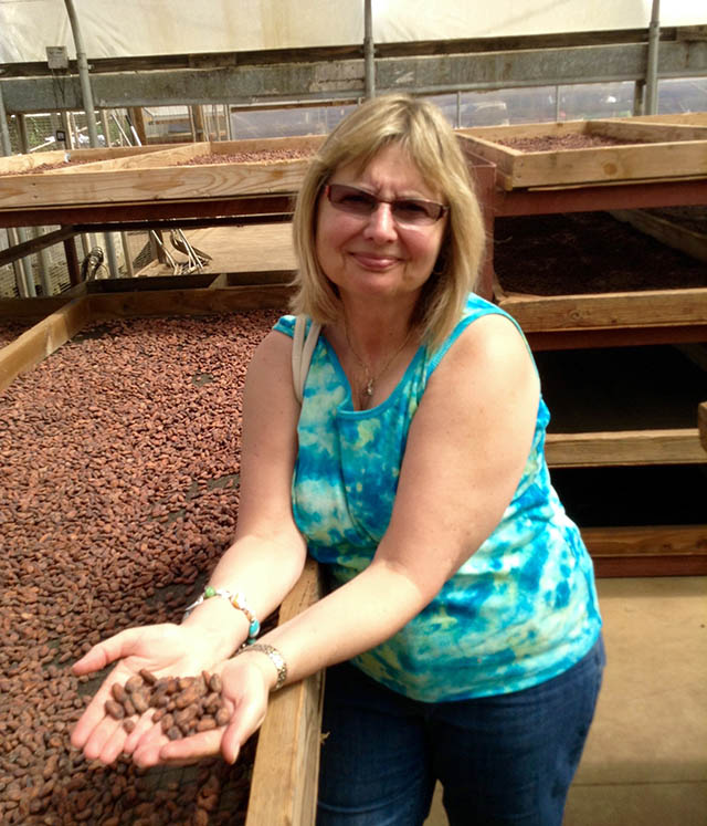 Doreen with drying cocoa pods in the sun