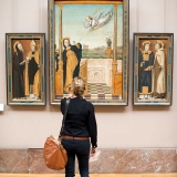 Taking in paintings at the Louvre, Paris, France