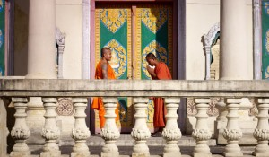 Two young buddhist monks meeting and saluting in a temple, Phnom, Penh, Cambodia, Asia.