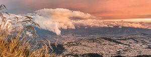 a view of quito, ecuador with clouds and sunset