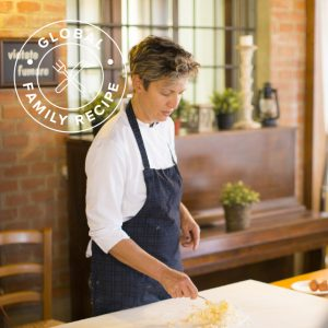 A woman making pasta on a cutting board