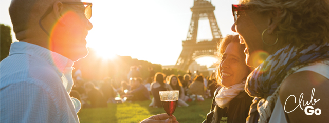 a picture of three people at sunset enjoying a glass of wine in front of the eiffel tower