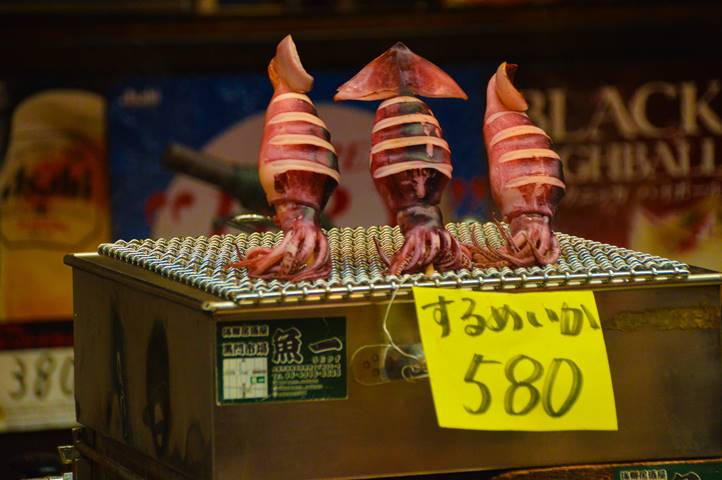 a picture of squid skewered on a grill with a price tag in front