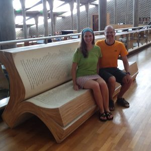 A man and a woman sitting together on a bench that is shaped like an open book.