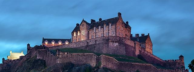Edinburgh castle at night with lights in a few windows