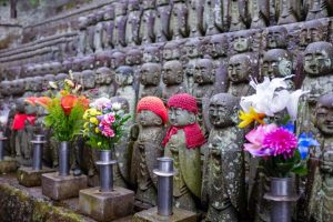 Small statues of Japanese people, a couple of which wearing knitted caps with artificial flowers in the foreground