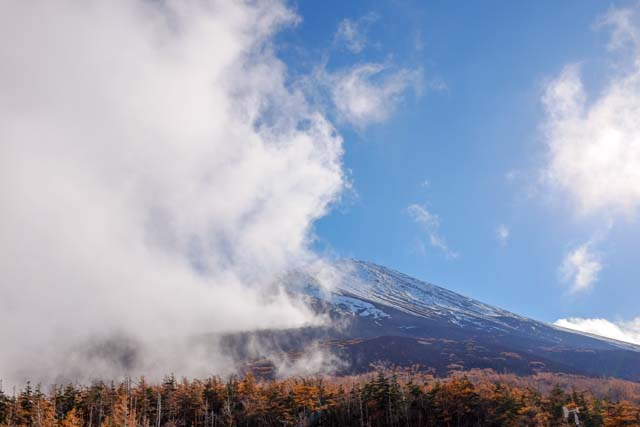 A picture of a snow-capped mountain partially covered by cloud against a blue sky