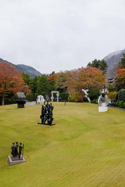A green hill with modern art sculptures on the lawn and fall foliage in the background