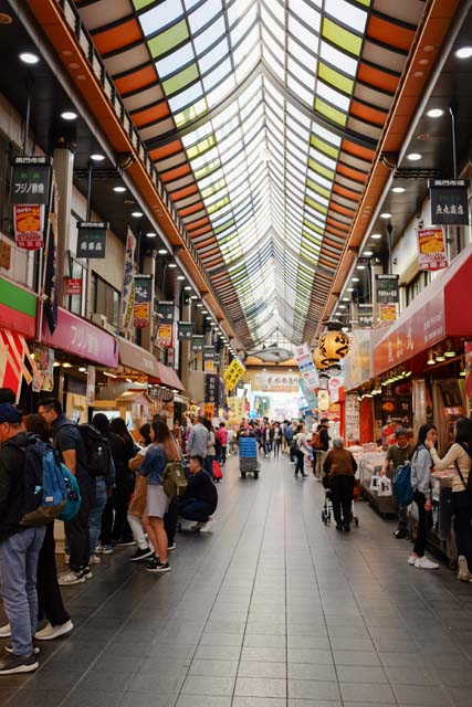 A busy shopping arcade with lots of people at many different stalls along the side and glass roof with light shining through