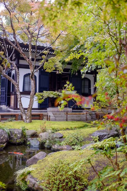 A Japanese temple behind lots of green foliage