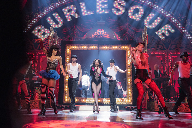 A photo of Cher performing on stage for the movie, Burlesque, with backup dancers and red lighting.