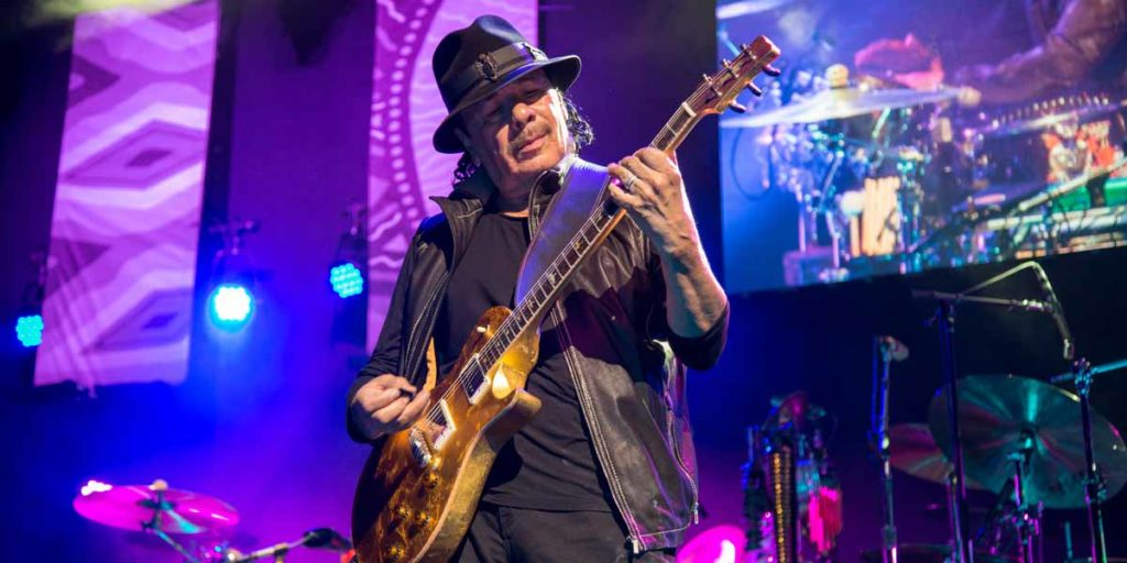 A photo of Santana playing the guitar on stage in Las Vegas, wearing a black hat.