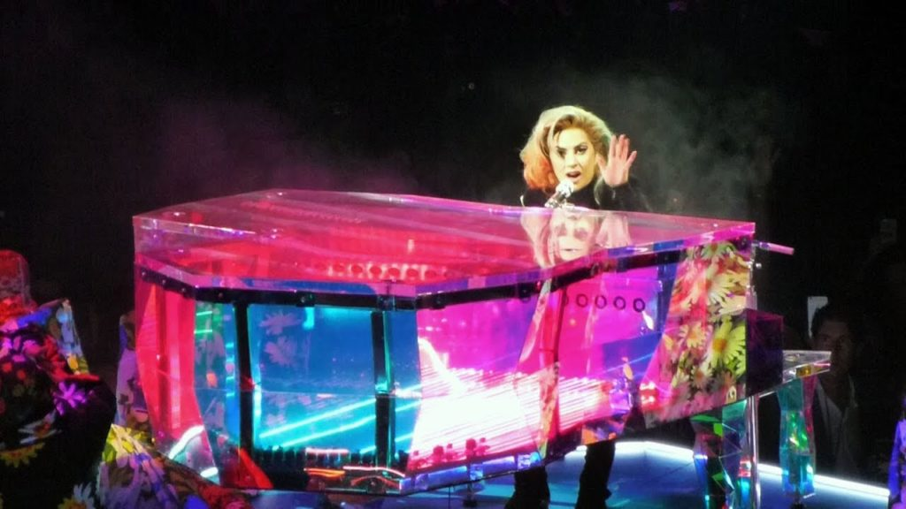 A photo of Lady Gaga performing in Las Vegas, playing a neon pink piano.