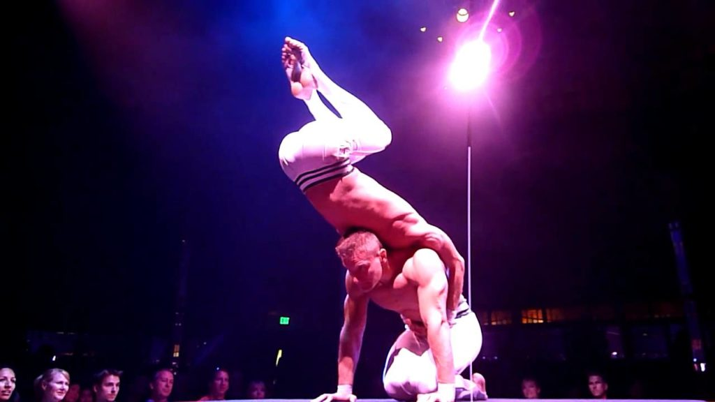 2 male performers, shirtless, performing in front of a Las Vegas crowd, with a pole and purple light behind them.