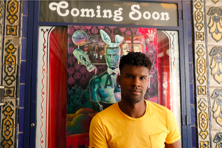 Serge Gay Jr, a local artist in San Francisco, poses in front of a poster promoting his new art show.