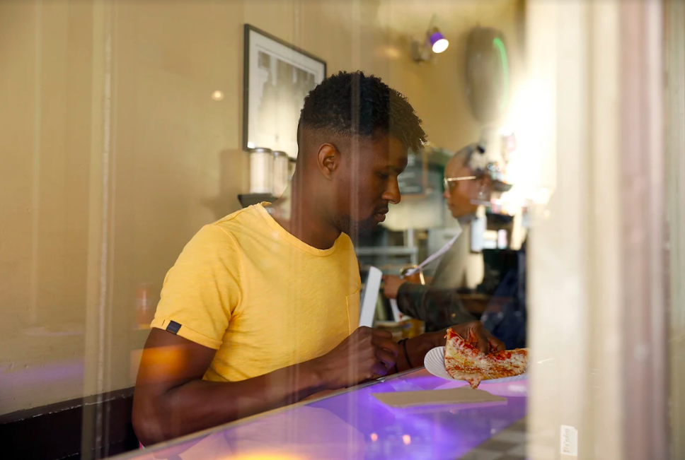 Serge Gay Jr. eating pizza in the Castro, taken through a window.