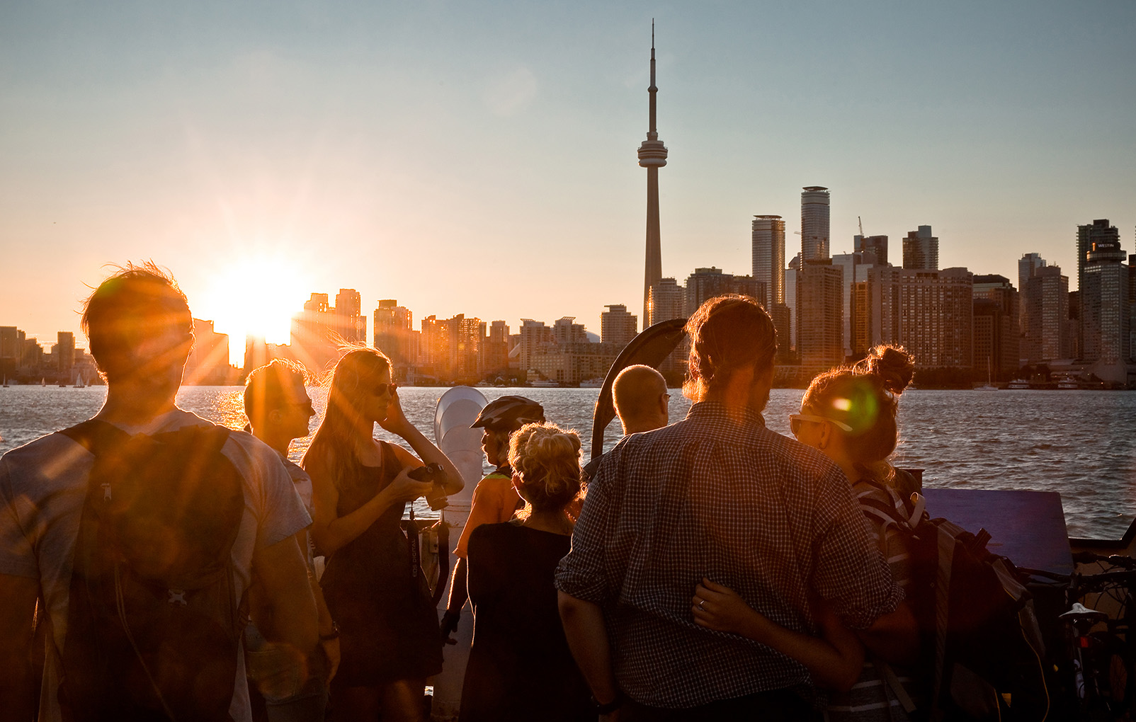 Travelers look at the CN tower in Toronto, aboard a boat closeby, with the sun beaming in the background.